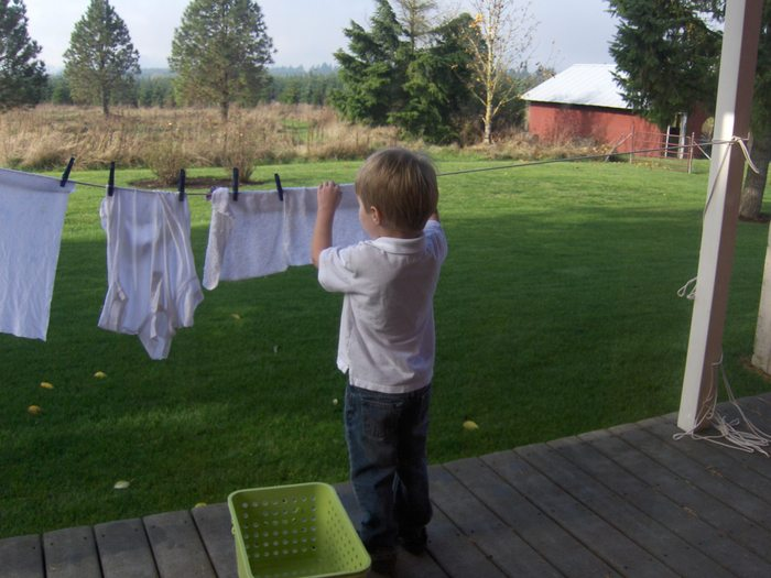 Augie hanging out laundry after having used an old-fashioned washboard, to his delight.